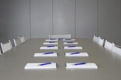 Witte notitieboekjes die op een grijze lijst voor negotia leggen Stock Afbeelding