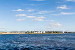 Witte Olietanks tussen Blauwe Hemel en Overzees Stock Foto