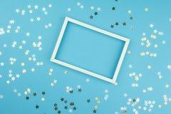 Witte omlijsting en lovertjessterren op blauwe achtergrond stock foto