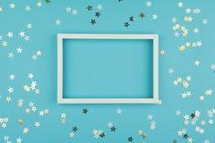 Witte omlijsting en lovertjessterren op blauwe achtergrond stock afbeeldingen