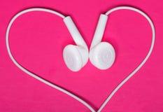 Witte oortelefoon op roze achtergrond, hart royalty-vrije stock afbeeldingen