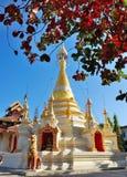 Witte pagode onder mooie duidelijke blauwe hemel De herfstbladeren als voorgrond Stock Afbeelding