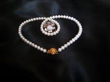 Witte parelhalsband met ringen op zwarte zijdeachtige achtergrond Royalty-vrije Stock Foto