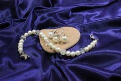 Witte pareljuwelen en overzeese steen op een blauwe achtergrond Handwork stock foto's