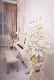 Witte piano dichtbij verfraaid Kerstboom Stock Foto