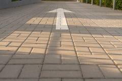 Witte pijl op de weg die van het bedekken plakken, op de richting wijzen stock afbeeldingen