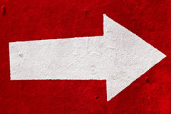 Witte pijl op het rode beton. Stock Afbeeldingen