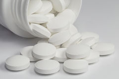 Witte pillen die uit pillenfles morsen Stock Foto