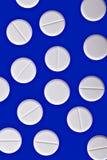 Witte pillen op blauw Royalty-vrije Stock Afbeeldingen