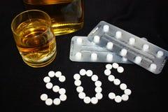 Witte pillen op zwarte achtergrond, welke het vormen zich het woords.o.s., met glas en fles alcohol Royalty-vrije Stock Afbeeldingen