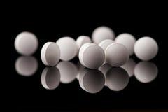 witte pillen op zwarte glasachtergrond Stock Afbeeldingen