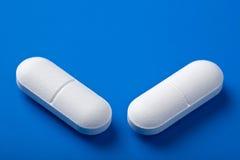 Witte pillen over blauw Stock Fotografie