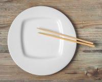 Witte plaat en eetstokjes voor sushi royalty-vrije stock afbeeldingen