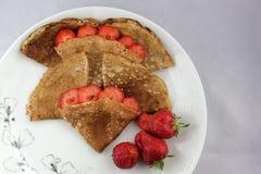 Witte plaat en uiterst kleine pannekoeken met aardbeien Stock Fotografie