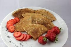 Witte plaat en uiterst kleine pannekoeken met aardbeien Stock Foto's