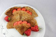 Witte plaat en uiterst kleine pannekoeken met aardbeien Royalty-vrije Stock Afbeelding