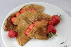 Witte plaat en uiterst kleine pannekoeken met aardbeien Royalty-vrije Stock Afbeeldingen