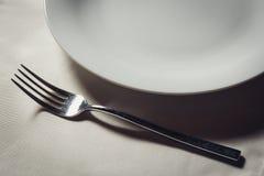 Witte plaat en vork op oude houten lijst Royalty-vrije Stock Fotografie