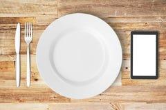 Witte plaat, het lege smartphonescherm, vork en mes op houten t Royalty-vrije Stock Fotografie