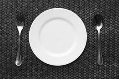 Witte plaat, mes en vork bij servet op houten royalty-vrije stock foto's
