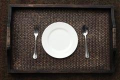 Witte plaat, mes en vork bij servet op houten royalty-vrije stock fotografie