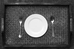 Witte plaat, mes en vork bij servet op houten stock foto