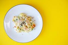 Witte plaat met aardappels en groenten op gele lijst stock afbeelding