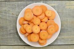 Witte plaat met beste voedsel voor oog-besnoeiing wortelen op houten Stock Afbeeldingen