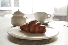 Witte plaat met croissant met kop van verse zwarte koffie Stock Fotografie