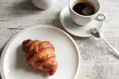 Witte plaat met croissant met kop van verse zwarte koffie Stock Foto's