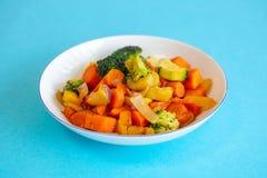 Witte plaat met gemengde groenten op blauwe lijst Stock Foto