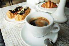 Witte plaat met Koffie eclairs en croissant met kop van verse zwarte koffie Stock Afbeeldingen