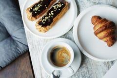Witte plaat met Koffie eclairs en croissant met kop van verse zwarte koffie Stock Foto