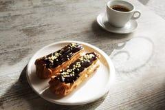 Witte plaat met Koffie eclairs met kop van verse zwarte koffie Stock Afbeeldingen