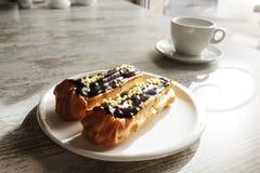 Witte plaat met Koffie eclairs met kop van verse zwarte koffie Royalty-vrije Stock Afbeeldingen