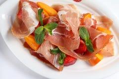 Witte plaat met smakelijke vleessnacks op witte lijst Stock Afbeelding