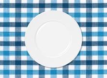 Witte plaat op blauw en wit tafelkleed stock illustratie