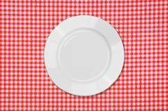 Witte plaat op rood en wit tafelkleed Royalty-vrije Stock Fotografie