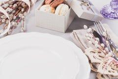 Witte plaat, purper glas, bestek, huidige doos met makarons en pussy wilgentakjes royalty-vrije stock afbeelding