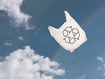 Witte plastic boodschappentas over hemel en regenboog, die in de wind blazen stock fotografie