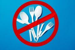 Witte plastic messen voor ??nmalig gebruik, lepels, vorken op een blauwe achtergrond Zeg nr aan plastiek voor ??nmalig gebruik Mi stock foto's