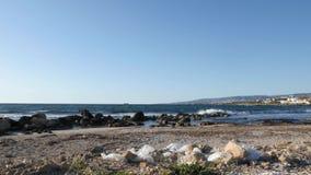 Witte plastic zakken op het rotsachtige strand met golven die klippen op de achtergrond raken Het Concept van de strandverontrein stock videobeelden