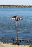 witte plofony in metaalbeeldhouwwerk met een lantaarnpaal met een achtergrond van blauwe rivier en brug stock foto's