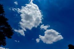 Witte, pluizige wolken in blauwe hemel Stock Fotografie