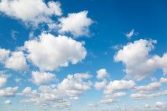 Witte, pluizige wolken in blauwe hemel.