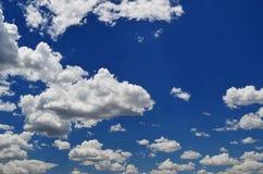 Witte pluizige wolken in een blauwe hemel Royalty-vrije Stock Foto's