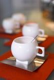 Witte porselein moderne koppen op sinaasappel gevoelde onderleggers voor glazen Royalty-vrije Stock Afbeelding
