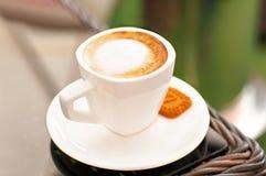 Witte porseleinkop van zwarte koffie met melk op rotanlijst Stock Fotografie