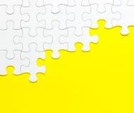Witte puzzel op gele achtergrond Stock Afbeeldingen