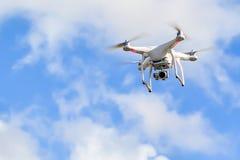 Witte quadcopterhommel met camera in een blauwe hemel stock foto's